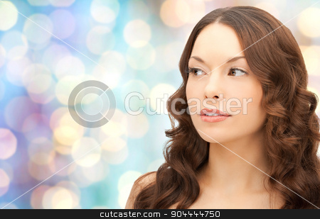 beautiful young woman face stock photo, beauty, people and health concept - beautiful young woman face over blue holidays lights background by Syda Productions