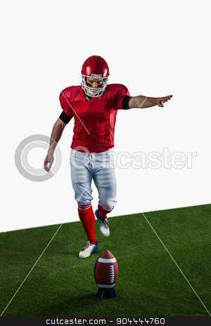 American football player kicking football stock photo, American football player kicking football on american football field by Wavebreak Media