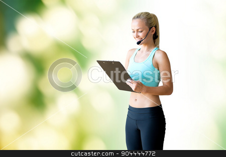 happy woman trainer with microphone and clipboard stock photo, fitness, sport and people concept - happy woman sports trainer with microphone and clipboard over green natural background by Syda Productions