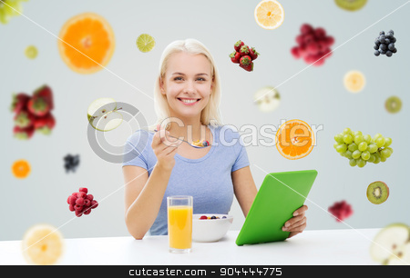 smiling woman with tablet pc eating breakfast stock photo, healthy eating, dieting and people concept - smiling young woman with tablet pc computer eating breakfast over fruits and berries on gray background by Syda Productions
