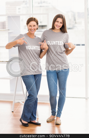Smiling female volunteers showing their shirts stock photo, Portrait of smiling female volunteers showing their shirts in the office by Wavebreak Media
