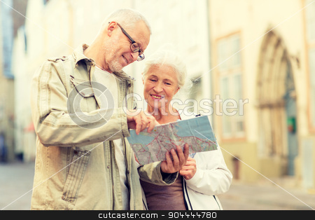 senior couple on city street stock photo, family, age, tourism, travel and people concept - senior couple with map and city guide on street by Syda Productions