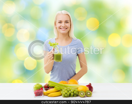 smiling woman drinking juice or shake at home stock photo, healthy eating, vegetarian food, diet, detox and people concept - smiling woman drinking green vegetable juice or shake from glass over summer green holidays lights background by Syda Productions