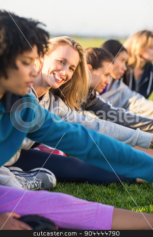 Smiling sporty blonde stretching during fitness class stock photo, Portrait of smiling sporty blonde stretching during fitness class in parkland by Wavebreak Media