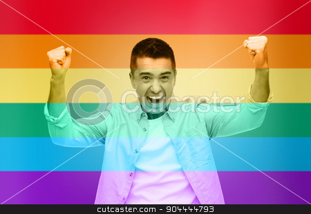 angry man with raised hands over rainbow flag stock photo, gesture, emotions, homophobia and people concept - angry gay man with raised hands over rainbow flag stripes background by Syda Productions