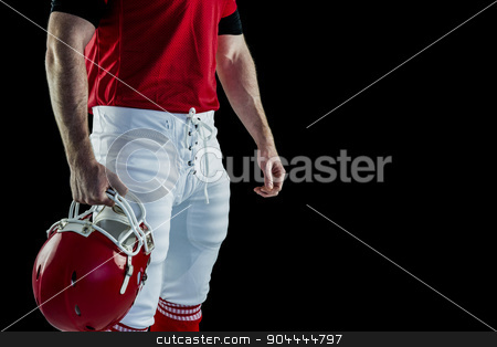 American football player holding his helmet stock photo, American football player holding his helmet against black background by Wavebreak Media
