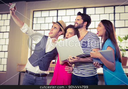 Grimacing friends taking selfies stock photo, Grimacing friends taking selfies at coffee shop by Wavebreak Media