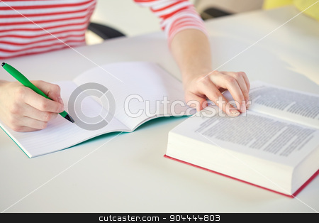 close up of female hands with book and notebook stock photo, people and education concept - close up of female hands with book or textbook writing to notebook at school by Syda Productions