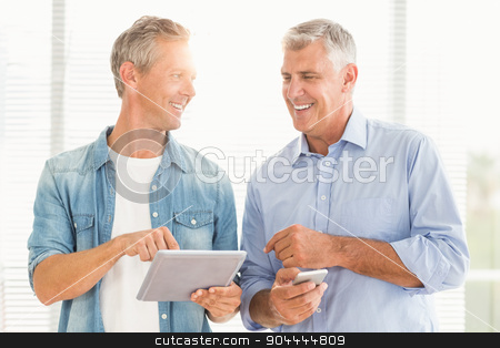 Business colleagues working on tablet and phone stock photo, Smiling business colleagues working on tablet and phone at office by Wavebreak Media
