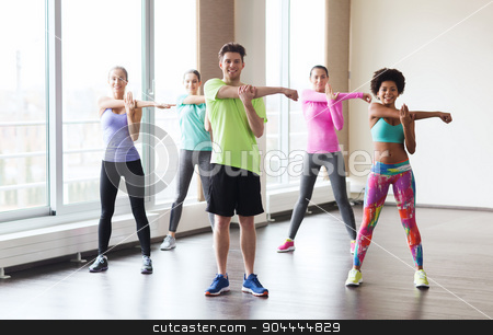 group of smiling people stretching in gym stock photo, fitness, sport, training, gym and lifestyle concept - group of smiling people stretching in gym by Syda Productions