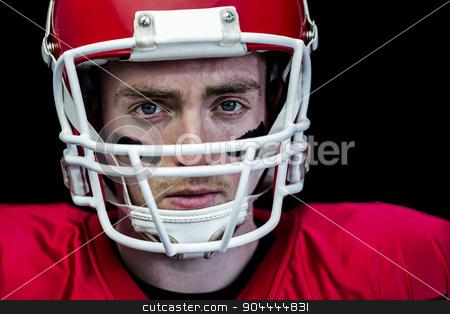 Portrait of focused american football player wearing his helmet stock photo, Portrait of focused american football player wearing his helmet against black background by Wavebreak Media