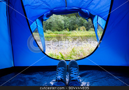 close up of camper legs lying near tent entrance stock photo, camping, travel, tourism, hike and people concept - close up of camper legs lying near blur tent entrance and enjoying natural landscape by Syda Productions