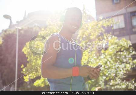 A handsome athlete using his phone stock photo, A handsome athlete using his phone on a sunny day by Wavebreak Media