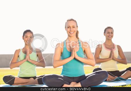 Smiling sporty women doing lotus pose stock photo, Portrait of smiling sporty women doing lotus pose in parkland by Wavebreak Media