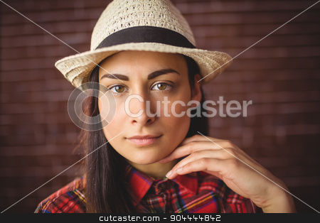 Beautiful hipster looking at camera stock photo, Beautiful hipster looking at camera on red brick background by Wavebreak Media