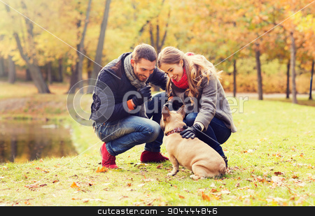 smiling couple with dog in autumn park stock photo, care, animals, family, season and people concept - smiling couple with dog in autumn park by Syda Productions