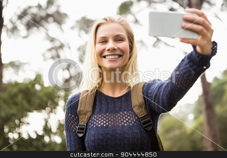 Smiling female hiker taking a selfie stock photo, Smiling female hiker taking a selfie with smartphone by Wavebreak Media