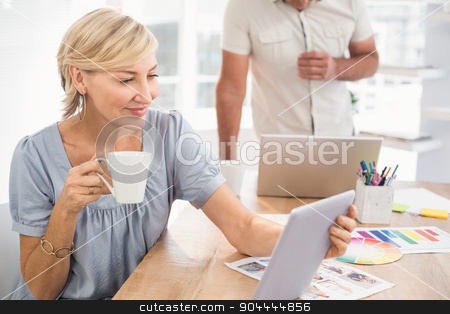 Smiling businesswoman holding a tablet stock photo, Businesswoman holding a tablet and drinking coffee at office by Wavebreak Media