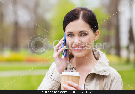 smiling woman with smartphone and coffee in park stock photo, drinks, leisure, technology and people concept - smiling woman with coffee calling and talking on smartphone in park by Syda Productions