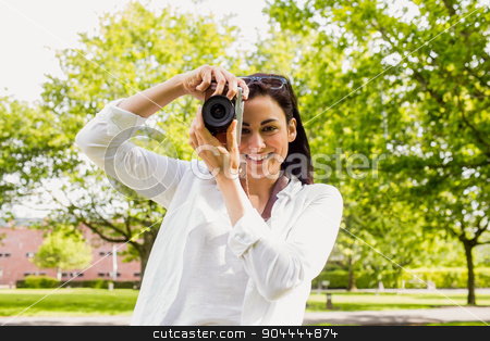 Beautiful brunette taking photo in the park stock photo, Beautiful brunette taking photo in the park on a sunny day by Wavebreak Media
