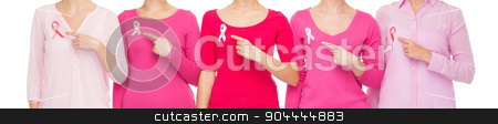 close up of women with cancer awareness ribbons stock photo, healthcare, people, gesture and medicine concept - close up of women in blank shirts pointing fingers to pink breast cancer awareness ribbons over white background by Syda Productions