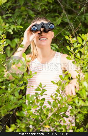 Smiling blonde looking through binoculars  stock photo, Smiling blonde looking through binoculars in the nature by Wavebreak Media