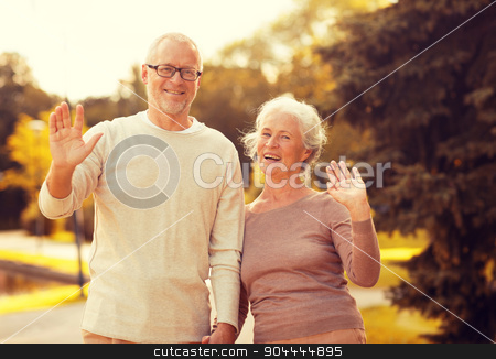 senior couple hugging in city park stock photo, family, age, tourism, gesture and people concept - senior couple waving hands in city park by Syda Productions