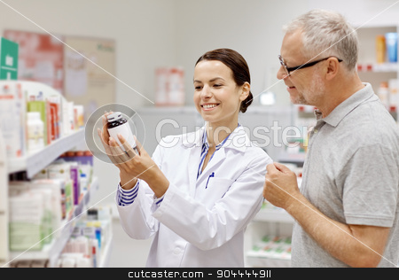 pharmacist showing drug to senior man at pharmacy stock photo, medicine, pharmaceutics, health care and people concept - happy pharmacist showing drug to senior man customer at drugstore by Syda Productions