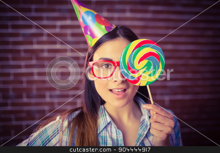 Pretty hipster with party hat and lollipop stock photo, Pretty hipster with party hat and lollipop on red brick background by Wavebreak Media