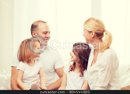 smiling family with two little girls at home stock photo, family, children and home concept - smiling family with two little girls at home by Syda Productions
