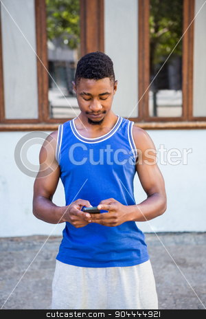 An handsome athlete using his phone stock photo, An handsome athlete using his phone on a sunny day by Wavebreak Media