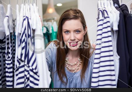 Brunette smiling through clothes rail stock photo, Brunette smiling through clothes rail in fashion boutique by Wavebreak Media