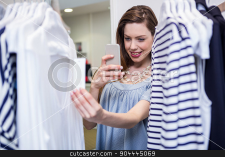 Brunette taking a photo of price tag stock photo, Brunette taking a photo of price tag in fashion boutique by Wavebreak Media