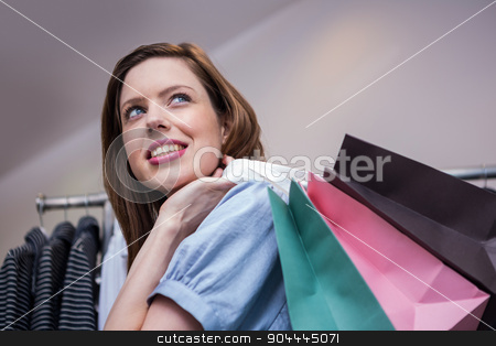 Woman holding shopping bags over shoulder stock photo, Woman holding shopping bags over shoulder in fashion boutique by Wavebreak Media