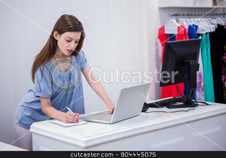 Shop worker using laptop by the till stock photo, Shop worker using laptop by the till in fashion boutique by Wavebreak Media