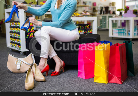 Woman trying on different shoes stock photo, Woman trying on different shoes in fashion boutique by Wavebreak Media
