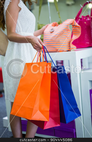 Pretty woman shopping for bags stock photo, Pretty woman shopping for bags at the shopping mall by Wavebreak Media
