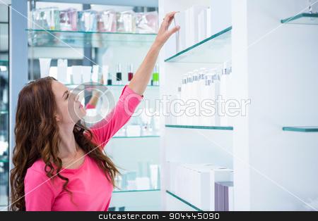 Pretty woman shopping for cosmetics stock photo, Pretty woman shopping for cosmetics at the pharmacy by Wavebreak Media