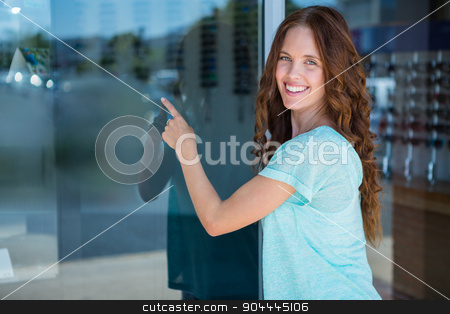 Pretty woman pointing at window stock photo, Pretty woman pointing at window at the optometry store by Wavebreak Media