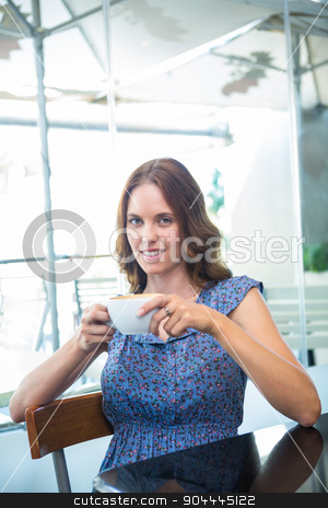 Pretty brunette smiling at camera stock photo, Pretty brunette smiling at camera in a coffee shop by Wavebreak Media