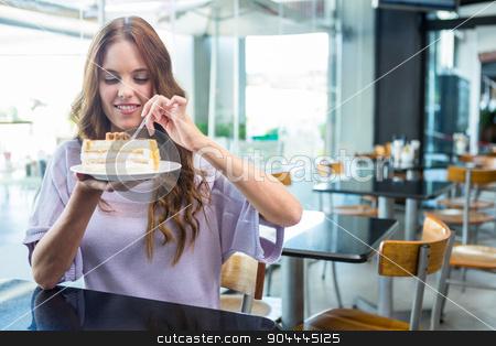 Pretty brunette enjoying a cake stock photo, Pretty brunette enjoying a cake in a coffee shop by Wavebreak Media