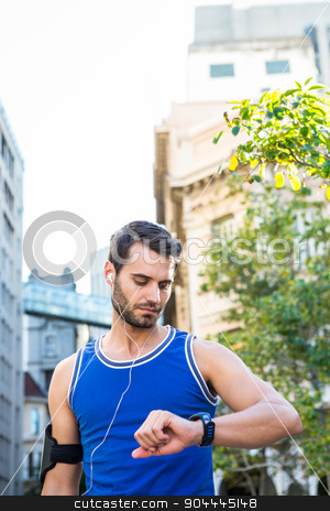 Handsome athlete checking heart rate watch stock photo, Handsome athlete checking heart rate watch in the city by Wavebreak Media