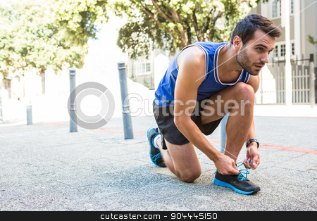 Handsome athlete tying his shoes stock photo, Handsome athlete tying his shoes in the city by Wavebreak Media