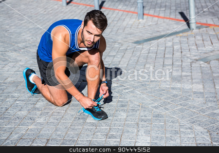 Handsome athlete tying his shoes on a sunny day stock photo, Handsome athlete tying his shoes on a sunny day in the city by Wavebreak Media
