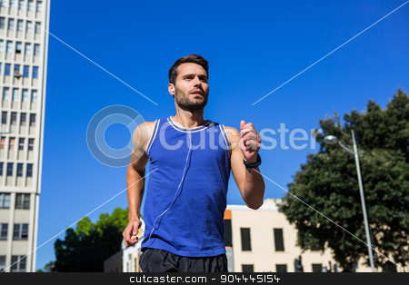 Handsome athlete jogging against blue sky stock photo, Handsome athlete jogging against blue sky in the city by Wavebreak Media