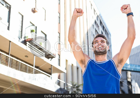 Happy handsome athlete triumphing stock photo, Happy handsome athlete triumphing in the city by Wavebreak Media