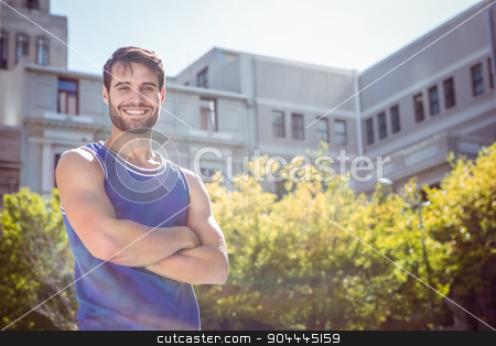 Smiling handsome athlete with arms crossed stock photo, Portrait of smiling handsome athlete with arms crossed in the city by Wavebreak Media