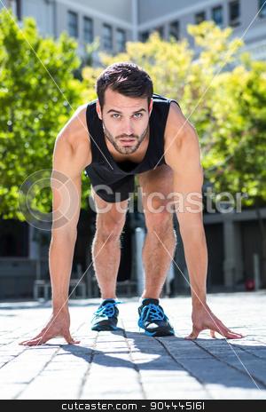 Handsome athlete in running stance stock photo, Portrait of an athlete in running stance on a sunny day by Wavebreak Media