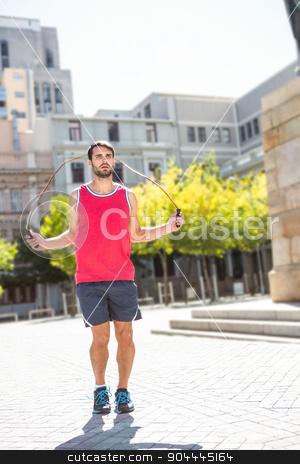 Handsome athlete doing jumping rope stock photo, Handsome athlete doing jumping rope on a sunny day by Wavebreak Media