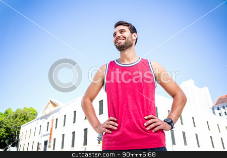 Smiling handsome athlete with hands on hips stock photo, Smiling handsome athlete with hands on hips looking away by Wavebreak Media